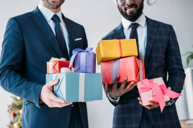 cropped image of smiling multicultural businessmen holding gift boxes in office