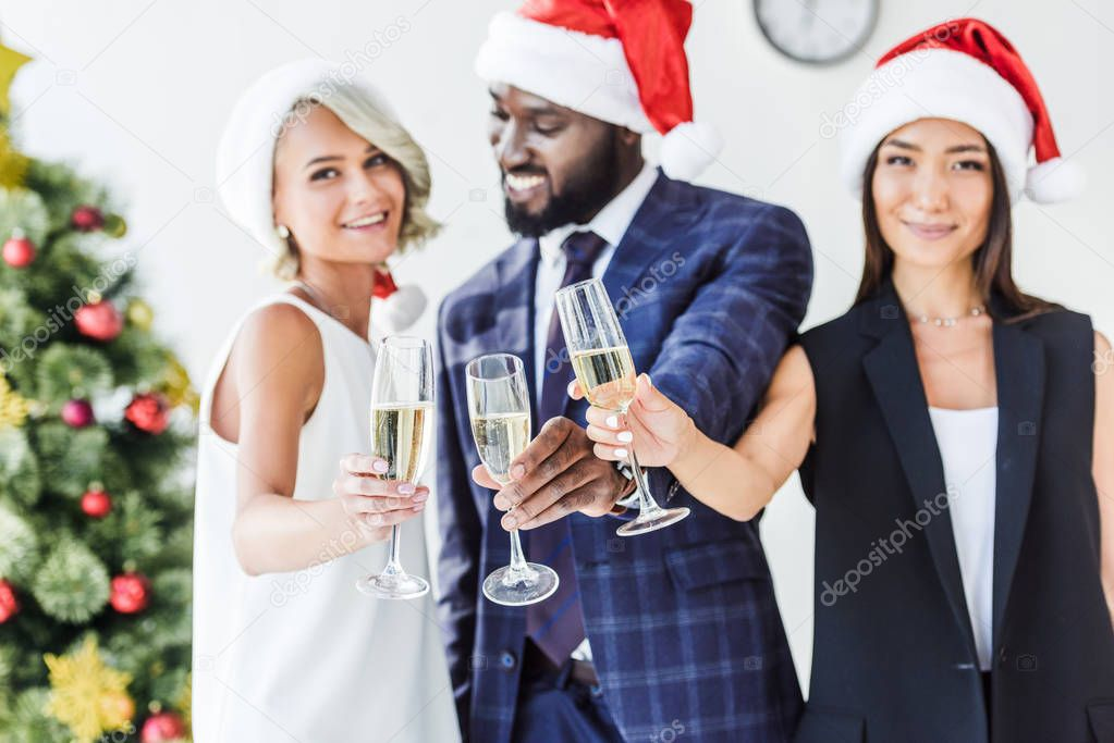 Selective focus of multiethnic businesspeople in santa hats clinking with glasses of champagne in office