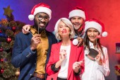 Fotografie multikulturní podnikatelé drží rty a brýle na hole na novoroční firemní party