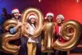 Fotografie multikulturní podnikatele a podnikatelky drží 2019 balónky na novoroční firemní party
