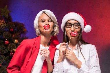 multicultural businesswomen in santa hats holding fake lips on sticks at new year corporate party
