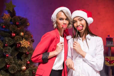 multiethnic businesswomen holding fake lips on sticks at new year corporate party