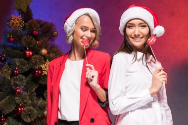 multicultural businesswomen holding fake lips on sticks at new year corporate party