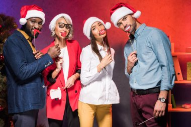multicultural businesspeople holding lips and mustaches on sticks at new year corporate party