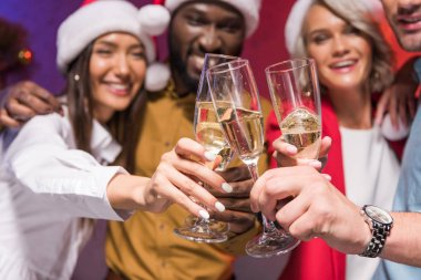 selective focus of multicultural businesspeople clinking with glasses of champagne at new year corporate party