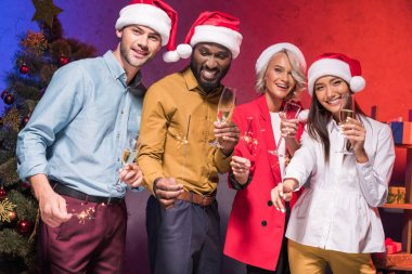 young multicultural businesspeople holding christmas sparklers and glasses of champagne at new year corporate party