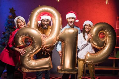 young multiethnic businesspeople in santa hats holding 2019 balloons at new year corporate party