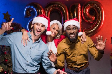 happy multicultural businesspeople in santa hats dancing at new year corporate party