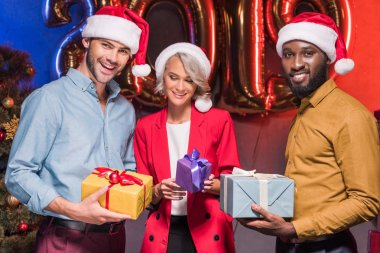 happy multicultural businesspeople in santa hats holding presents at new year corporate party