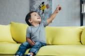 lächelnder kleiner Junge zeigt nach oben, während er zu Hause auf dem gelben Sofa sitzt