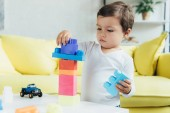 Fotografie adorable little boy playing with constructor blocks and toys at home