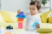 roztomilý chlapeček hraje s konstruktor bloků a hračky doma