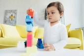 roztomilé dítě hrát si s barevnými konstruktor bloky na stole doma