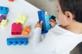 oříznutý pohled chlapce hrát s barevnými konstruktor bloky