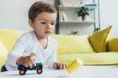 Rozkošné dítě hraje s modré autíčko doma