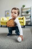 Fotografie Rozkošné dítě hraje s baseballovou rukavici a míč doma