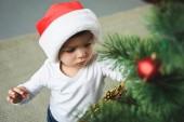 niedlicher Junge mit rotem Weihnachtsmann-Hut schmückt den Weihnachtsbaum