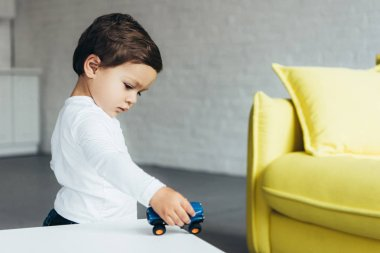 adorable kid playing with toy car at home
