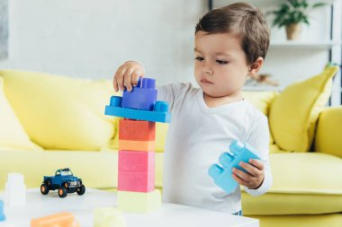 adorable little boy playing with constructor blocks and toys at home