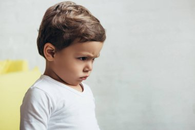 portrait of little offended boy in bad mood at home