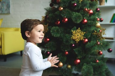 adorable smiling boy near christmas tree at home