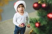 entzückendes Kind mit Weihnachtsmütze schmückt Weihnachtsbaum mit Kugeln