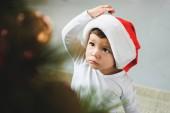 entzückende Kleinkind in weihnachtsmütze Weihnachtsbaum zu betrachten