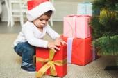 roztomilé dítě v čepice santa s dárky u vánočního stromu