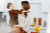 Fényképek boldog fiatal anya és lánya, miközben főzés Hálaadás Pulyka együtt átfogó