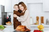 Fotografie beautiful young mother and daughter embracing and looking at camera while cooking thanksgiving turkey together