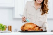 cropped shot of woman cooking thanksgiving turkey at kitchen