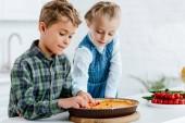 Fotografie entzückende Geschwister dekorieren Pumpking-Torte mit Beeren zusammen in Küche