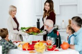 smiling women carrying delicious baked turkey for thanksgiving dinner with big family
