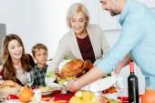 šťastná žena starší a dospělé muže, který má pečené Turecko díkůvzdání večeře s rodinou