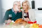 šťastný starší pár s poháry mluvit sloužil stolu pro oslavu díkůvzdání
