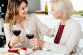 s úsměvem dospělých žena cinkání sklenice na víno s starší matky sloužil stolu pro oslavu díkůvzdání