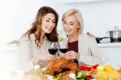 atraktivní pro dospělé žena cinkání sklenice na víno s starší matky sloužil stolu pro oslavu díkůvzdání
