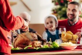cropped image of woman slicing delicious tukey for christmas dinner with happy family at home