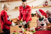 smiling man and woman carrying turkey for holiday dinner while little kid in christmas hat sitting on grandfather knees at table