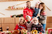 Fotografie smiling family celebrating christmas at table with holiday dinner at home