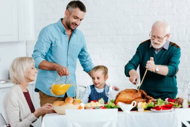 grandfather slicing turkey while adult man pouring juice at served table for thanksgiving celebration with family