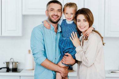 portrait of happy family holding and embracing little daughter and looking at camera at kitchen