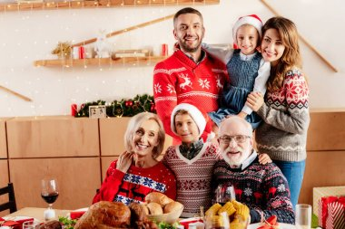 smiling family celebrating christmas at table with holiday dinner at home