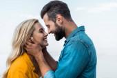 boční pohled na usmívající se pár objímat a políbí proti modré obloze