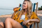atraktivní dívka sedí na lehátku a pití piva na písečné pláži