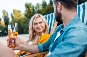 Fotografie couple sitting on sun loungers and clinking with glass bottles of beer on sandy beach