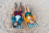 Fotografie high angle view of couple lying on sun loungers with beer in bottles on sandy beach