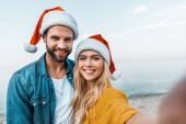kamery z pohledu usmívající se pár v santa klobouky při pohledu kamery na pláži