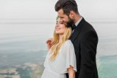 happy wedding couple in suit and white dress hugging on beach