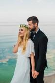 Fotografia sposi in abito bianco e vestito tenendosi per mano e distoglie lo sguardo sulla spiaggia